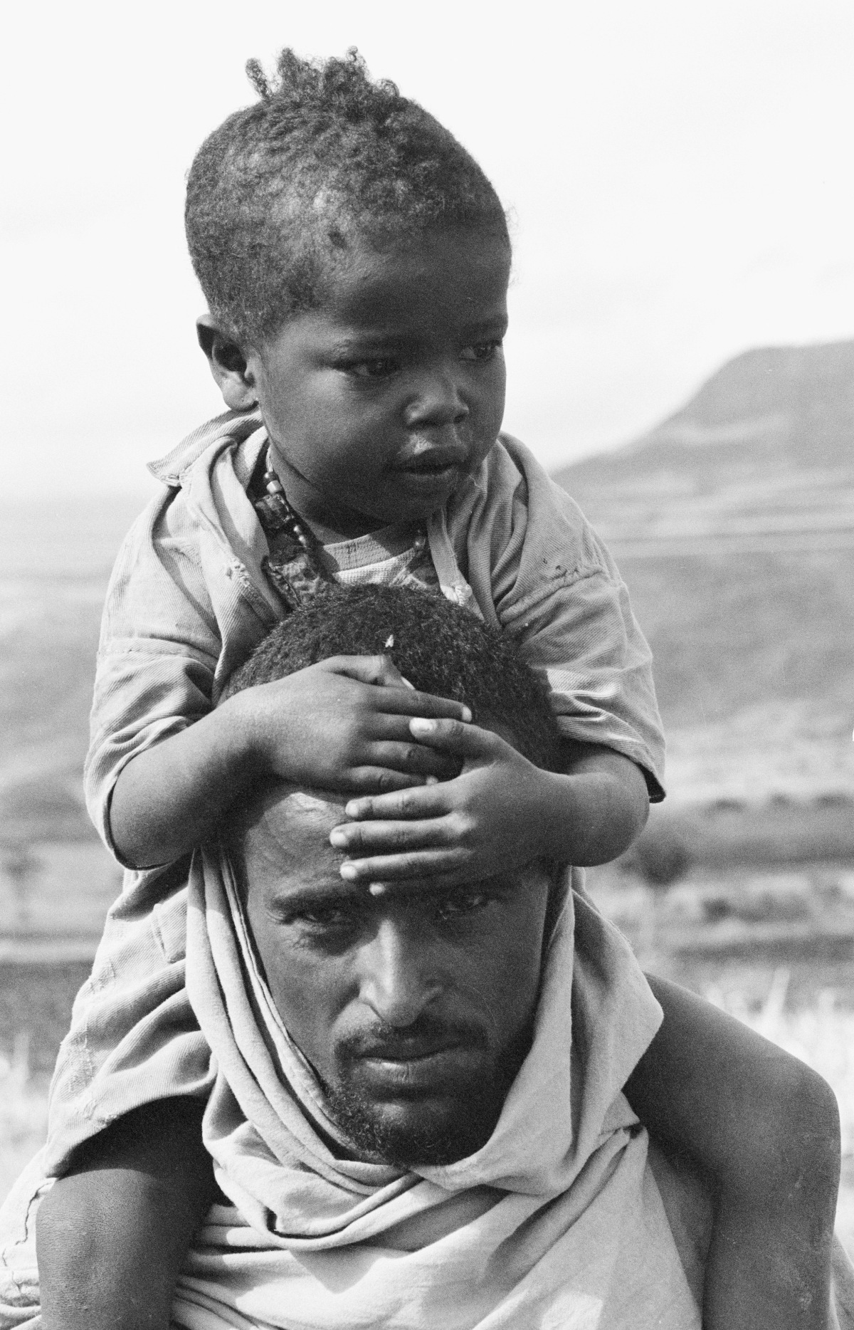 A child sits on his father's shoulders as they wait for food at a drought relief centre in the north-eastern town of Bati. Emergency food supplies and medicine are being rushed to relief centres in Bati and other drought-stricken areas.  In 1984 in Ethiopia, a severe drought has resulted in a devastating famine, killing more than 1 million people and leaving 7 million others facing malnutrition and starvation. Food and water are among the urgent necessities. The office of the United Nations High Commissioner for Refugees (UNHCR), the Food and Agriculture Organization (FAO), and UNICEF are among the international organizations that have rushed emergency assistance to famine-afflicted areas. UNICEF relief supplies include food, vaccines, blankets and water supply equipment. UNICEF, which estimates that, at minimum, more than 500,000 tonnes of food will be needed for 1985, is seeking an additional US $12.5 million in funding to help mitigate the crisis.