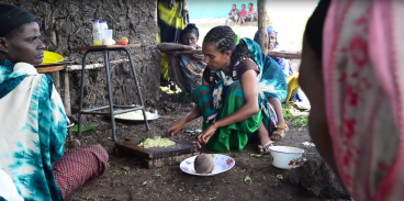 Meseret Haile, with her son Mikias on her back, prepares food at a community information session on nutrition at the Wolargi health post, in Ethiopia's Oromia region.