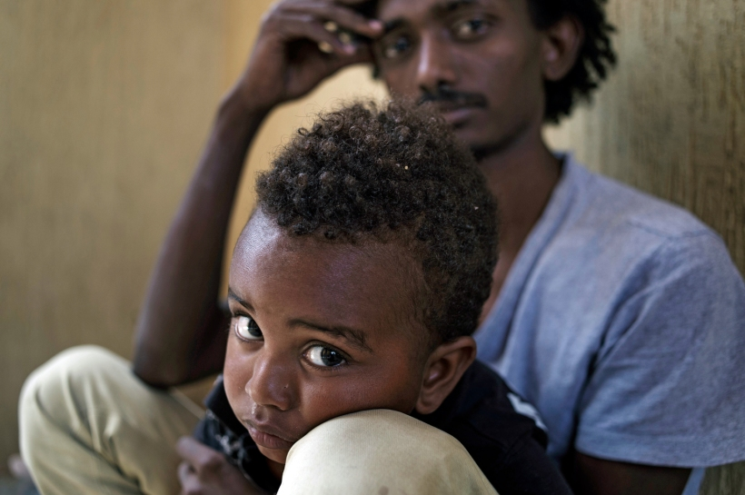 """On 24 May 2015 in Libya, Addis, holding his 30-month-old son, Lato, sits in a cell at the Alguaiha detention centre in the coastal town of Garabulli on the north-western coast. The detention facility houses illegal migrants apprehended while attempting the dangerous voyage across the Mediterranean Sea to reach Europe. Foreigners without legal immigration status in the country can be arrested and can spend up to 12 months in a detention centre, where conditions are poor at best, with inadequate medical care, insufficient relief items, and without proper ventilation and sanitation. Overcrowding also exacerbates the already harsh conditions and, with poor ventilation, can lead to the spread of disease. In some detention centres, more than 50 people are crowded into rooms designed for 25. Addis, from Eritrea, is now a single parent. He and his wife decided to leave their homeland right after Lato was born. The family spent two years in Sudan, where Addis worked as a driver. """"After that, we decided to go to Tripoli, where my brother is working in a supermarket,"""" he said. His wife died during the journey by truck between Sudan and Libya. """" …my wife had an asthma attack. We could[n't] do anything for her, """"Addis said. """"She quickly died, suffocated."""" He buried her under the sand, with the help of another man making the crossing. """"Now I am here in this detention centre because, as we were only 200 kilometres from Tripoli, the police caught us at a check point. My dream is still to join my brother in Tripoli and offer a better life to my son, """"he said."""